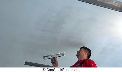 Plasterer apply plaster with trowel on ceiling. Static shot.