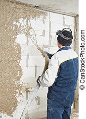 Plasterer at indoor wall renovation decoration spraying liquid plaster from plastering station