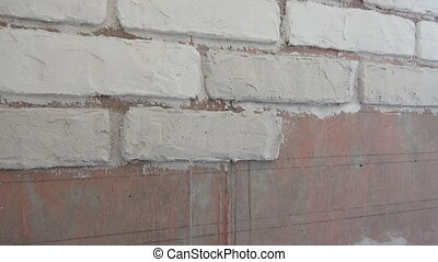 Plasterer hand plasters imitation of bricks on the wall