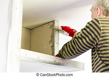 Plasterer home improvement handyman worker with putty knife working on apartment wall filling. Home renovation concept