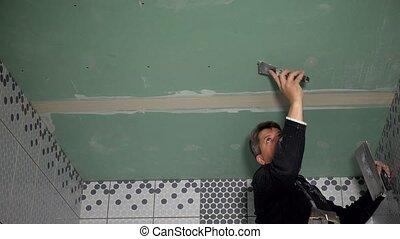 Plasterer man spackling gypsum plasterboard ceiling with ...