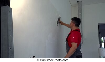 Plasterer man spackling wall with putty. New apartment ...