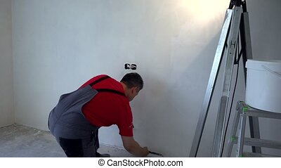 Plasterer man wit trowel apply plaster on wall. New ...