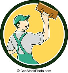 Illustration of a plasterer masonry tradesman construction worker standing with trowel looking to the side viewed from rear set inside circle on isolated background done in cartoon style.