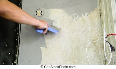 Plasterer plastering with a spatula wall near power socket...