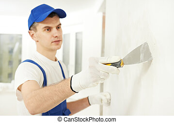 Plasterer with putty knife at wall filling - Plasterer home...