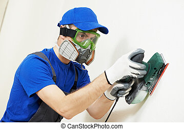 plasterer worker with sander at wall filling - Home...