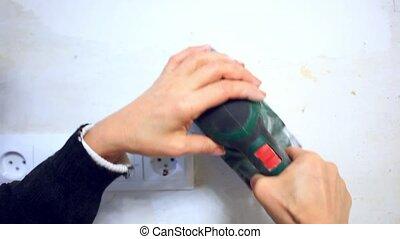 plastering female hand sanding the plaster in white wall....