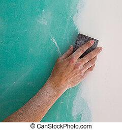 plastering man hand sanding the plaste in drywall seam...