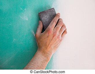 plastering man hand sanding the plaste in drywall seam plasterboard