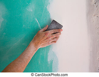 plastering man hand sanding the plaste in drywall seam...