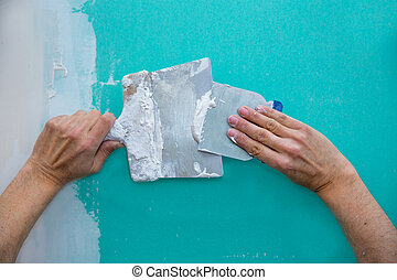 Plastering man hands with plaste on drywall plasterboard ...