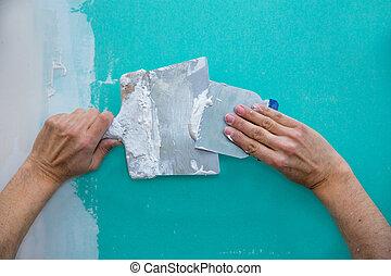 Plastering man hands with plaste on drywall plasterboard