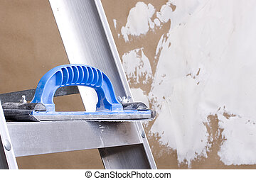 Plastering trowel laying on a step ladder next to a brown ...