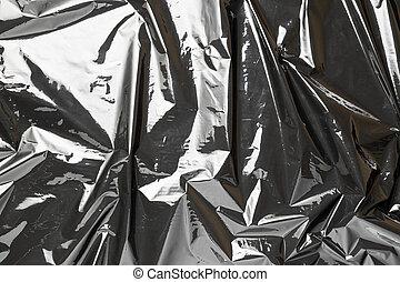 Plastic bag. Wrap transparent dark cellophane texture. Black shiny film pattern. Creative crumpled background.