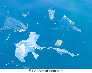 plastic bags and debris floating in the sea - plastic...