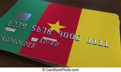Plastic bank card featuring flag of Cameroon. Cameroonian national banking system related animation