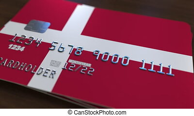 Plastic bank card featuring flag of Denmark. National banking system related animation