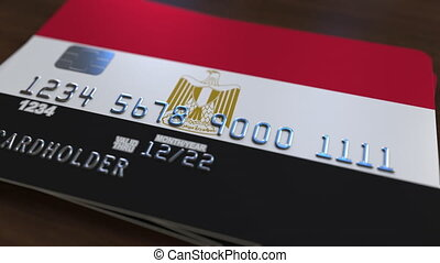 Plastic bank card featuring flag of Egypt. National banking...