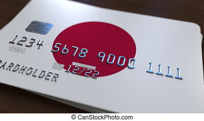 Plastic bank card featuring flag of Japan. National banking system related animation