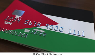 Plastic bank card featuring flag of Jordan. Jordanian...