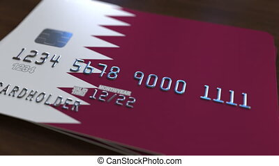 Plastic bank card featuring flag of Qatar. Qatari banking...