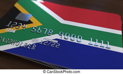 Plastic bank card featuring flag of South Africa. National banking system related animation