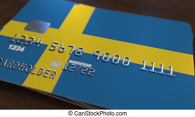 Plastic bank card featuring flag of Sweden. National banking...