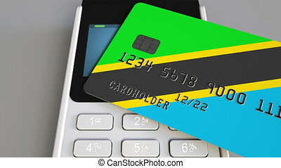 Plastic bank card featuring flag of Tanzania and POS payment...
