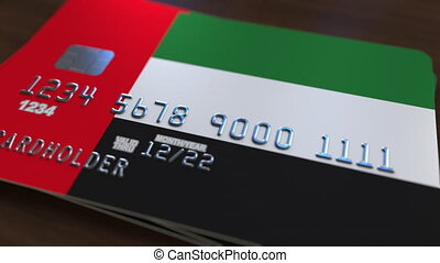 Plastic bank card featuring flag of the United Arab Emirates, UAE. National banking system related animation