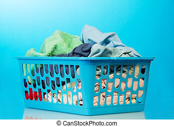 Plastic basket with clothes washing on blue background.