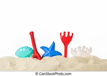 Plastic beach toys in sand isolated on white