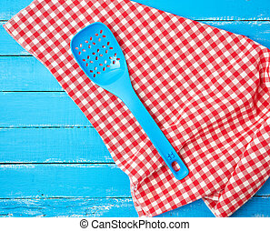 plastic blue spoon with holes on a red textile napkin
