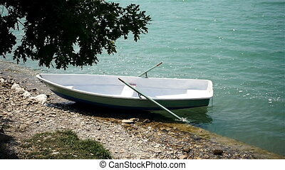 Plastic Boat With Wood Seats Swinging On The Waves Near The Shore In Azure Water