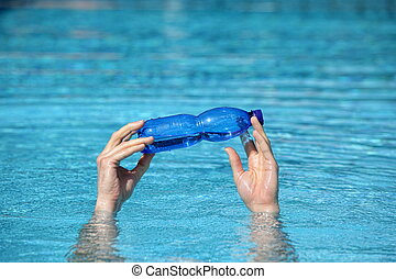 two hands holding plastic bottle of water above surface of water