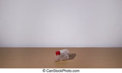 Plastic bottle bends into a lump in stop motion on white background
