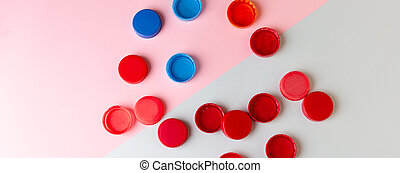 Plastic bottle caps for drinking water on a colored ...
