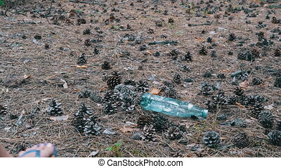 Plastic Bottle in a Pine Forest. Woman Stepping on a Plastic Bottle with his Foot