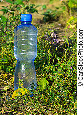 Plastic bottle of drinking water on the ground