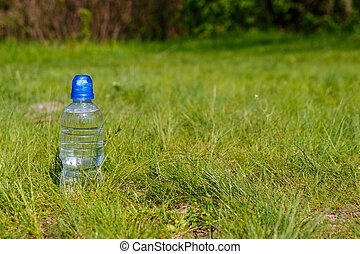 Plastic bottle with fresh drinking water in green grass on meadow