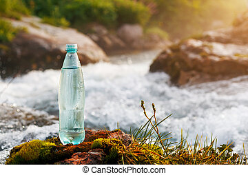 Plastic bottle with fresh drinking water on the background of a mountain stream, in the wild. ool fresh water