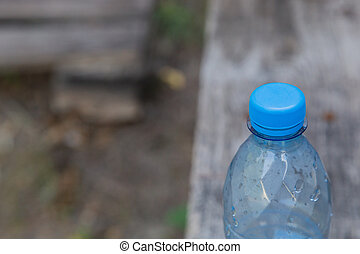 Plastic bottle with water on a wooden background.
