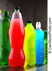 Plastic bottles of assorted carbonated soft drinks in...