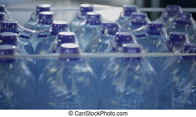 Plastic bottles with water in package, rotate in workshop of modern factory.