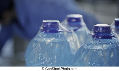 Plastic bottles with water in packaging stand in workshop of plant indoor.