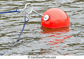 Plastic bouy in red with blue ropes, closeup