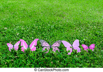 Plastic butterfly on green grass with copy space