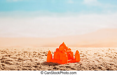 Plastic Castle in the sand on against sea.