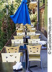 Plastic Chairs and Blue Umbrella at Restaurant Patio
