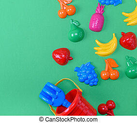 plastic childrens toys in the form of fruit and a bucket